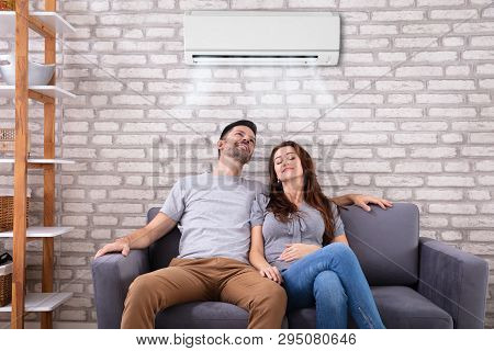 Happy Young Couple Sitting Under Air Conditioner On Couch At Home