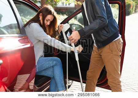 Smiling Young Husband Helping Her Disabled Wife With Crutches To Get Inside The Car