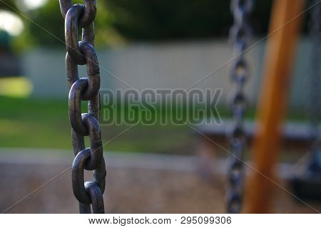 Close up view of chain hung horizontally with other chains heavily blurred background poster