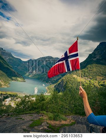 Norwegian flag and beautiful view over Geirangerfjorden from Flydalsjuvet viewing point. Tourist attraction. Tourism vacation and travel. poster