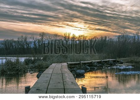 Gorgeous Sunset In The Sky Over A Wood Footpath At A Lake