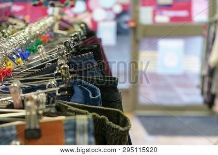 Detail Photo - Trousers And Jeans On Hangers In Charity Thrift Shop