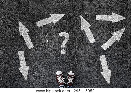 Man In Shoes Standing On Asphalt Next To Multitude Of Arrows In Different Directions And Question Ma