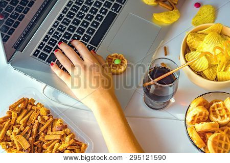 Girl Works At A Computer And Eats Fast Food. Unhealthy Food: Chips, Crackers, Candy, Waffles, Cola.