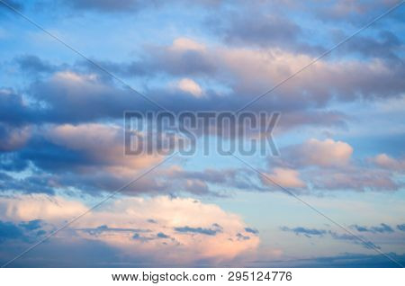 Blue sky background. Dramatic sunset cloudy sky with picturesque clouds lit by warm sunset sunlight. Natural sky background, sky sunny landscape. Sunny sky background, blue sky with white clouds