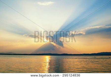 Sea sunset landscape - sea water lit by sunset summer light. Summer sunny water scene in colorful tones. Sea summer nature with mountain range at the horizon