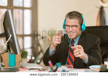 Professional Man In A Creative Office Listening To Headphones And Making A Silly Gesture