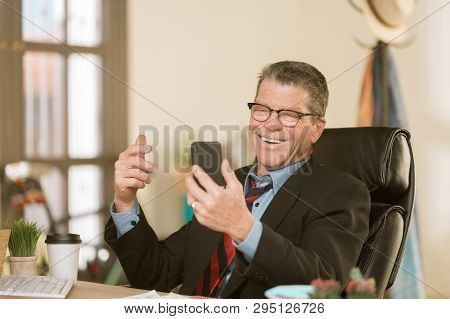 Cheerful Man Communicating Using Smart Phone In His Office