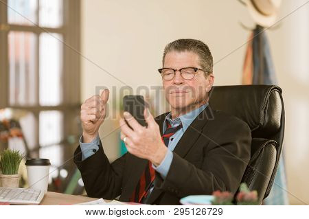 Professional Man Communicating Using Smart Phone In His Office With A Window