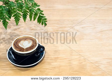 Coffee Cup On Wood Table With Fern Leaf