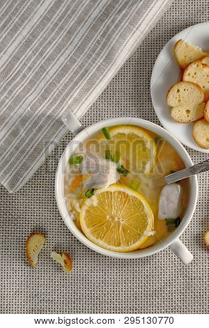Delicious Chicken Soup With Lemon, Rise, Carrot, Green Onion And Yellow Bruschette Chips Aside. Top