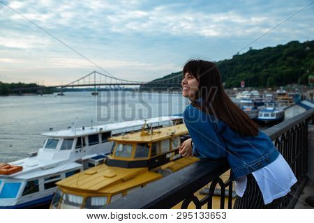 Young Pretty Woman Looking On River At Morning Time. Boats In Dock. Copy Space