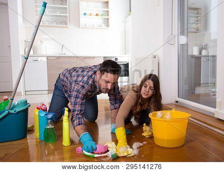 Young Couple Enjoying Housekeeping Together