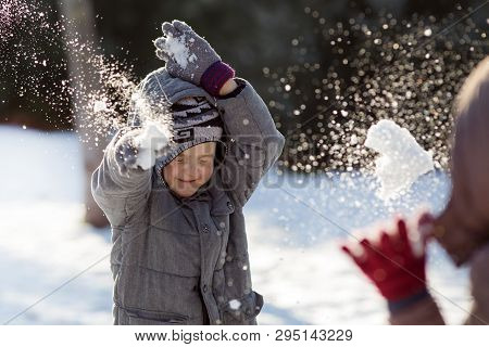 Boy And Girl Playing Snowball Fight On Cold Winter Day In Park