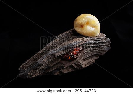 Natural amber. A piece of yellow opaque natural amber on large piece of dark stoned wood. poster