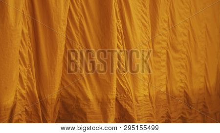 Yellow robe (of a Buddhist monk or novice); any of the three garments of the monk. The upper inner robe. Sarong, Yellow Fabric background / texture. poster