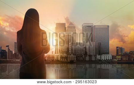 Young Woman Looking Over The Canary Wharf Business And Banking Aria With Skyscrapers At Sunset. Futu