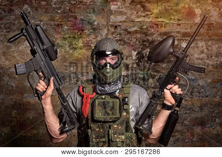 Paintball gamer with guns, strong handsome men in camouflage uniform