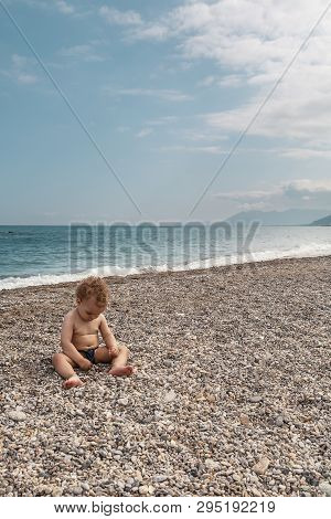 Lovely Boy Playing On The Beach In A Sunny Day