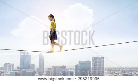 Cute joyful little girl walking on a rope over city. Mixed media