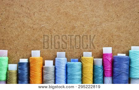 Multicolored Threads On A Roll For Sewing On A Blurred Wooden Background. With Copy Space