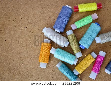 Multicolor Sewing Threads On A Roll For Sewing On A Wooden Background. With Copy Space