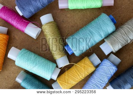 Multicolor Sewing Threads On A Roll For Sewing On A Wooden Background