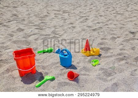 Childrens Toys On The Beach Sand Against Turquoise Sea.