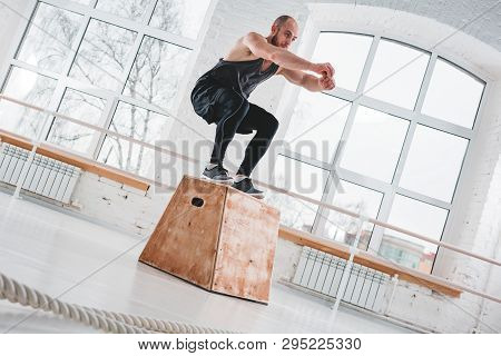 Bearded Athlete Male Jumping Over Wooden Box In Sport Gym. Fit Man Doing Jump Exercises For Strong B