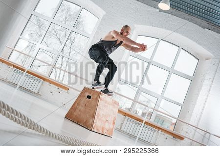 Strong Man Doing Jumping Exercises Over Box At A Cross Training Style Gym. Fit Sportsman Jump At Box