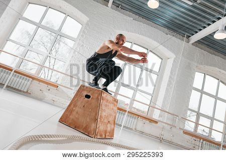 Fit Strong Athlete Jumping At Wooden Box In Cross Gym. Young Sportsman Doing Jump Exercises Over Box