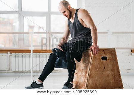 Sweaty Muscular Man Sitting On Box In Gym. Strong Male Athlete Resting After Hard Workout In Light H