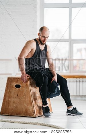 Perspiring Male Athlete Resting After Intense Cross Workout. Tired Sportsman Relaxing On Wooden Box