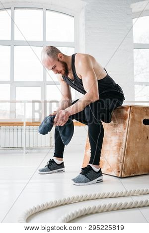Tired Strong Man Sitting On Box At Gym. Perspiring Fit Sportsman Resting After Hard Cross Workout In