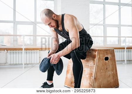 Tired Fit Man Resting After Hard Cross Training In Fitness Gym And Hold Towel In Hands. Male Athlete