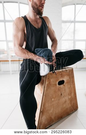 Closeup View On Sweaty Muscular Man Sitting On Box In Gym. Strong Male Athlete Resting After Hard Wo