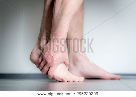 Causian Man Holds Hands To His Painful Feet, Pain In Foot