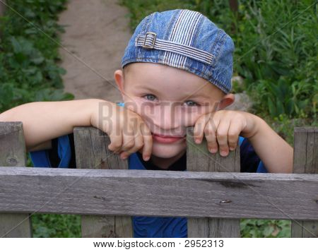 Little Boy Leaned Against The Fence