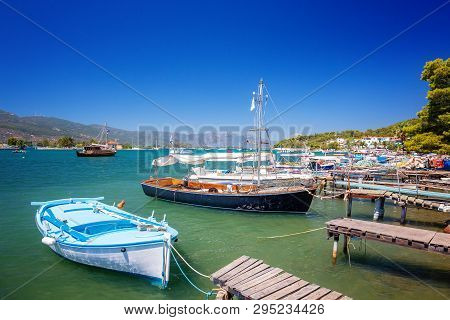 Poros Island In A Summer Day In Greece. Wooden Pier With Fishing Boats At Poros Island In Greece