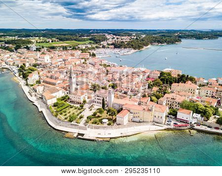 Croatian town of Porec, shore of blue azure turquoise Adriatic Sea, Istrian peninsula, Croatia. Bell tower, red tiled roofs of historical buildings, boat, piers. Euphrasian Basilica. Aerial view. poster