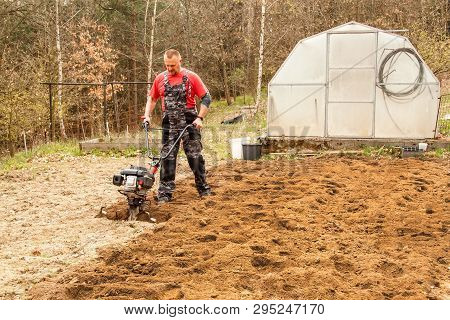 Spring Preparation Soil For Seeding With Tiller. Spring Work In The Garden. Farmer Plows The Land Wi