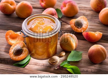 Apricot jam and ripe apricots on the wooden table.