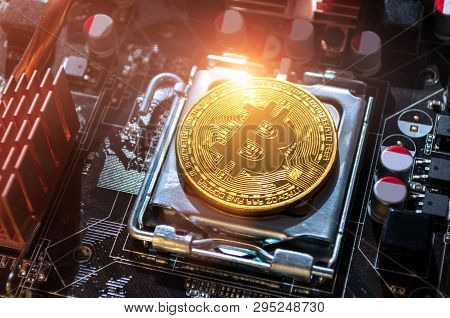 Golden bitcoin among the electronic computer details. Business concept of digital cryptocurrency. Bitcoin closeup. Blockchain technology, bitcoin mining concept