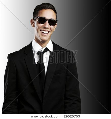 portrait of a young man wearing a suit and sunglasses against a black background poster