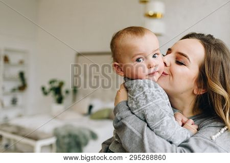 Beautiful Young Mother Kissing Her Cute Son Holding Him In Her Arms. Family, Togetherness.