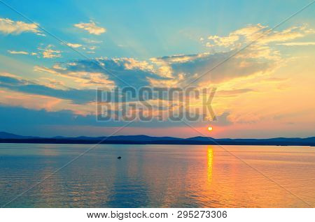 Ocean sunset landscape. Ocean water surface lit by sunset light. Summer sunny water scene in picturesque tones. Ocean summer nature with mountains at the horizon