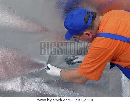 Trabalhador da construção civil aposição de folha de isolamento de vapor sob a superfície do sótão termicamente isolado