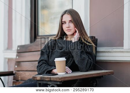 Young beautiful millenial girl in a coat is sitting on an outdor bench with a paper cup of coffee. Autumn or spring day, cool weather. poster