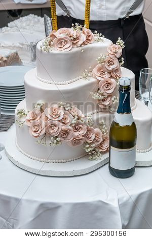 Three-tiered white wedding cake decorated with roses and champagne on restaurant table. poster