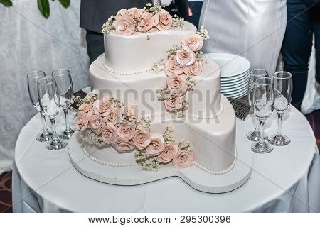 Three-tiered White Wedding Cake Decorated With Roses And Glasses For Champagne On Restaurant Table R